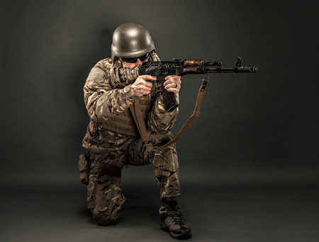 bullet camera: Studio shot of military man standing on one knee and aiming with rifle.