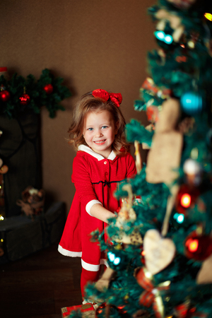 Standing girl puts decorations to a Christmas tree. Vertical indoors shot. Stock Photo