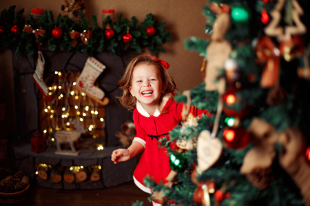 Smiling little girl peeping from behind Christmas tree in living room. Horizontal indoors shot Stockfoto