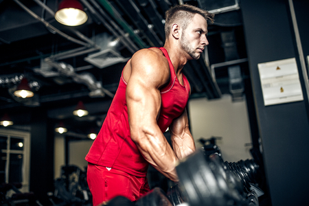 Handsome muscular man is working out and posing at a gym Stock Photo