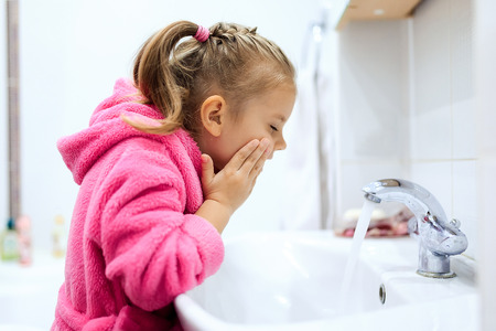 ponytail: Side view of cute little girl with ponytail in pink bathrobe washing her hands. Copyspace