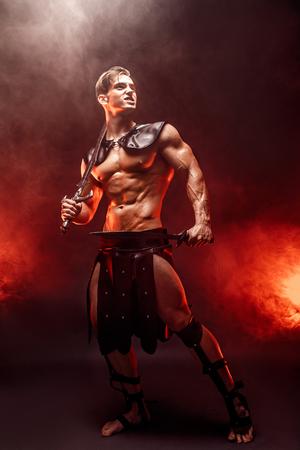Portrait en pied de sexy jeune guerrier tenant épée et en détournant les yeux tout en posant contre le feu. Copyspace Banque d'images