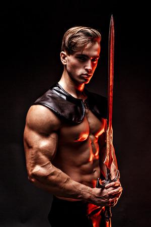 セクシーな筋肉男剣を押しながらカメラ目線の肖像画。
