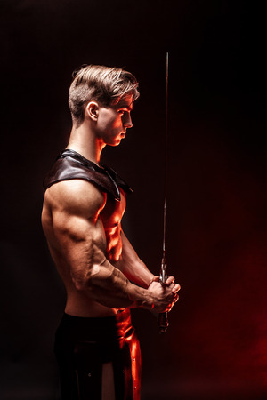 Portrait of sexy muscular concentrated man holding sword. Stock Photo