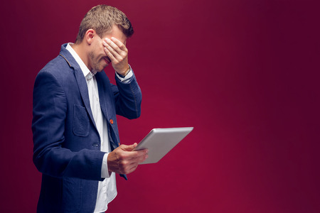 and the horizontal man: Disappointed man holding tablet and closed eyes with hand. Horizontal studio shot Stock Photo