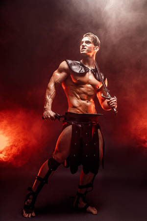 Full-length portrait of sexy young warrior holding sword and looking away while posing against fire. Copyspace