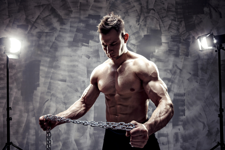 The Perfect male body. Awesome bodybuilder. One handsome sexual strong young man with muscular body holding rope with hand hanging on neck and shoulders standing posing in studio. strained biceps.