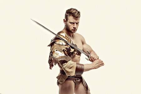 Portrait of muscular and strong gladiator in leather bagged clothes holding sword. Isolated.