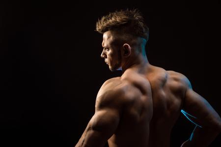 Hombre fuerte de la aptitud atlética que presenta los músculos de la espalda, tríceps, dorsal sobre fondo negro