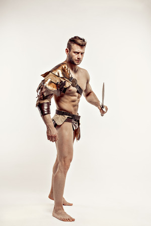Portrait of handsome strong gladiator in leather costume holding sword and looking away.Studio shot,isolated. Stock Photo