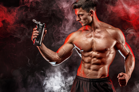 Muscular man with protein drink in shaker over dark smoke background 免版税图像 - 68653346