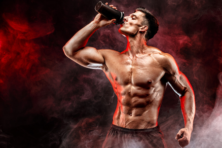 Gespierde man met eiwit drankje in de shaker over donkere rook achtergrond Stockfoto