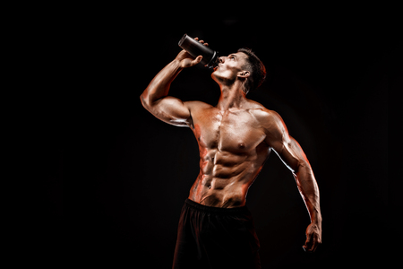 Muscular man with protein drink in shaker over dark background 스톡 콘텐츠