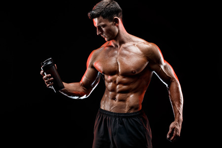 Muscular man with protein drink in shaker over dark background Stockfoto