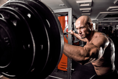 Bald Bodybuilder preparing for exercise with barbell in gym