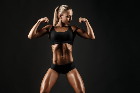 hardworker: You can say she is a hardworker. Shot of sporty female blonde girl showing off her perfect body on black background