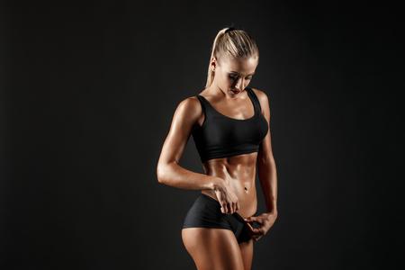 Se puede decir que es un hardworker. El tiro de la muchacha deportiva femenina rubia mostrando su cuerpo perfecto en fondo negro Foto de archivo - 69607934