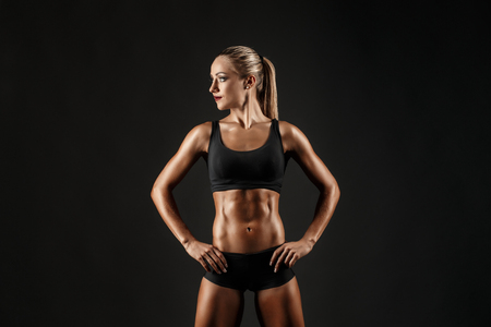 muscle toning: You can say she is a hardworker. Shot of sporty female blonde girl showing off her perfect body on black background