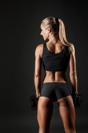 muscle toning: Shot of sporty female blonde girl showing back off her perfect body on black background