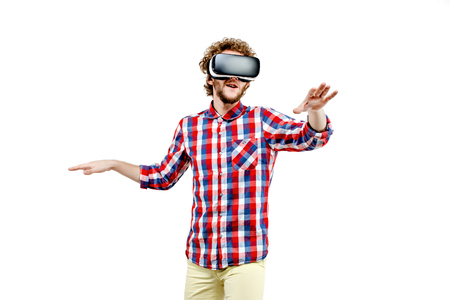 visualizing: Young curly-haired man in plaid shirt using a VR headset and experiencing virtual reality isolated on white background Stock Photo