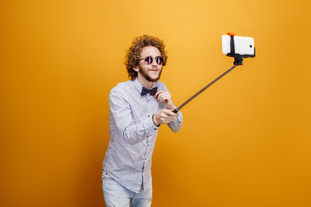 Curly-haired man in sunglasses and bow-tie taking selfie using monopod