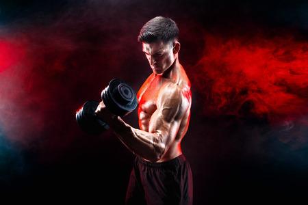 ダンベルで運動を行う筋肉男を集中してください。