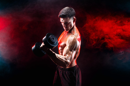 Concentrated muscular man doing exercise with dumbbell