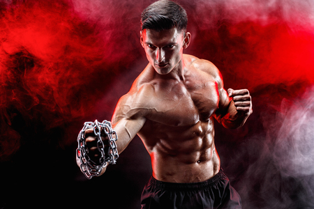Serious muscular fighter doing the punch with the chains braided over his fist. Stock Photo