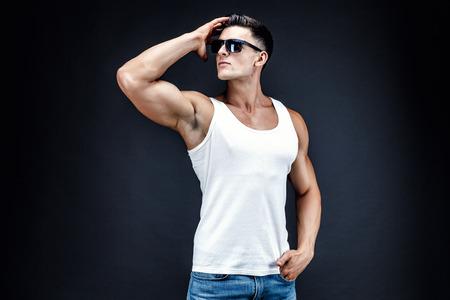 Stattlicher muskulöser Mann in den dunklen Gläsern und ein weißes Hemd.