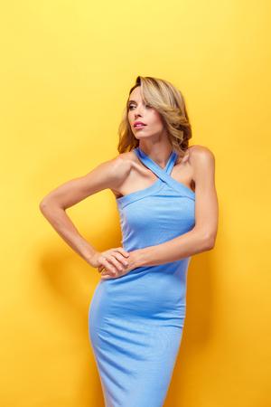 blue dress: Beautiful blonde model in blue dress posing at camera Stock Photo