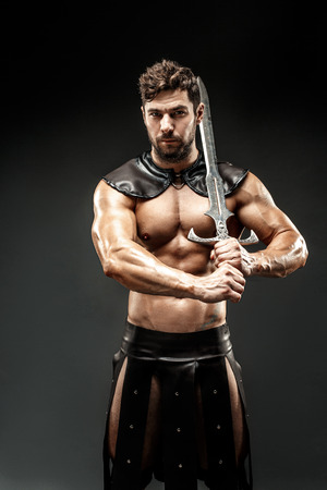 Severe barbarian in leather costume with sword Stock Photo