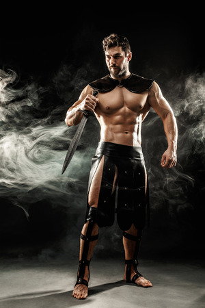 Severe barbarian in leather costume with sword in smoke