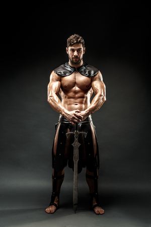 Severe barbarian in leather costume with sword 스톡 콘텐츠