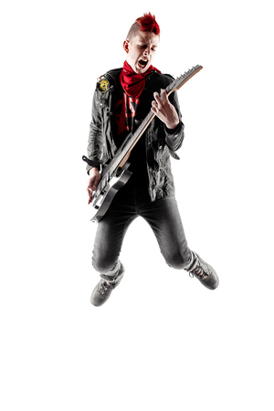 Teen with red mohawk jumping while playing guitar Stock Photo