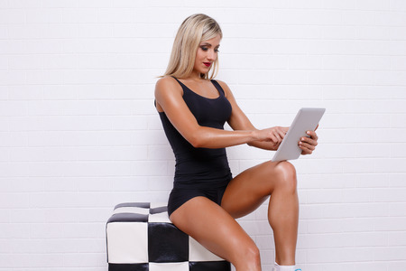 Sportive woman surfing the tablet