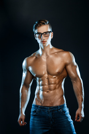 bodybuilder posing. Beautiful sporty guy male power. Fitness muscled man Archivio Fotografico