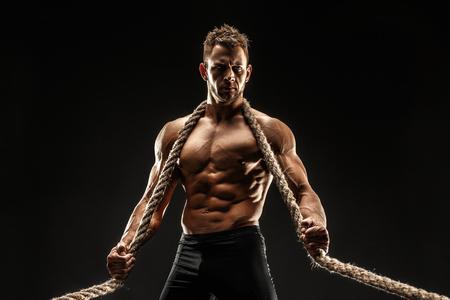 首や肩に掛かっている手でロープを保持している筋肉の体と 1 つハンサムな性的な強い若い男立っている黒い背景のスタジオでポーズをとる 写真素材 - 71069037