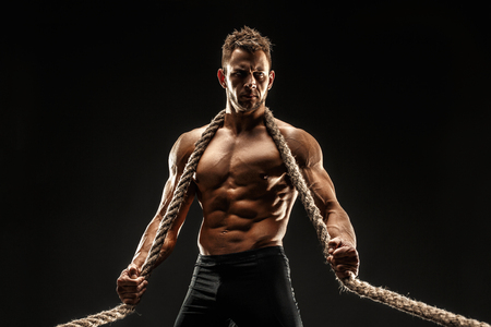 One handsome sexual strong young man with muscular body holding rope with hands hanging on neck and shoulders standing posing in studio on black background