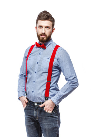 stylish guy wearing blue shirt, red bowtie and suspenders isolated on white. smile. stand. hands in the pocket. Foto de archivo