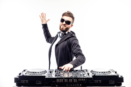 unemotional: Young stylish man in black sunglasses posing with hands up behind mixing console on white studio background.