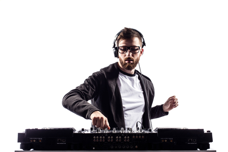 Young stylish man in glasses posing behind mixing console on white studio background.