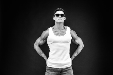 Handsome muscular man in dark glasses and a white shirt. Stock Photo