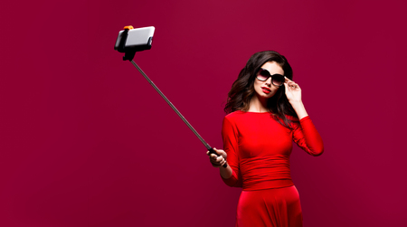 Portrait of beautiful brunette in awesome dress and red lips wearing sunglasses while making selfie with stick. Isolated Stock Photo