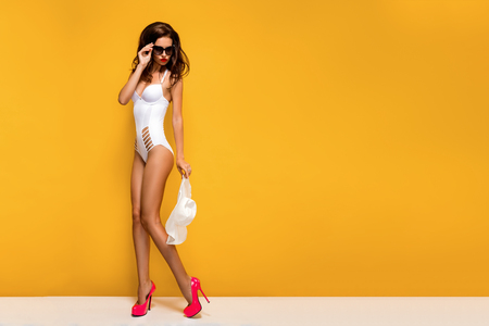 Stylish lady in sunglasses and white hat, bikini against of yellow background