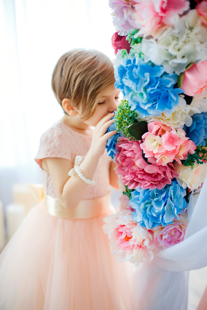 Little adorable girl in dress posing in decorated room among flowers.