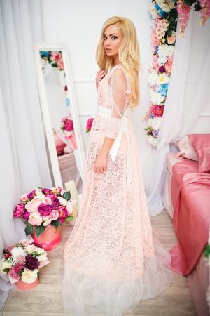 Young blonde pretty woman in romantic negligee stand near bed decorated with flowers and looking at camera.