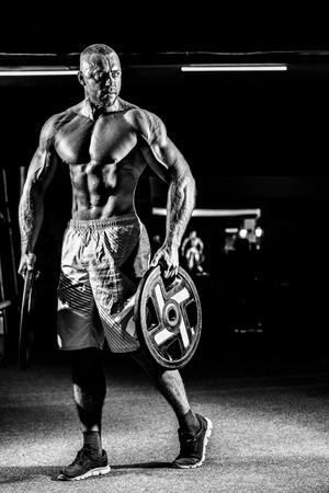 Macht athletischen Kerl stehend in der Turnhalle mit Hanteln Standard-Bild