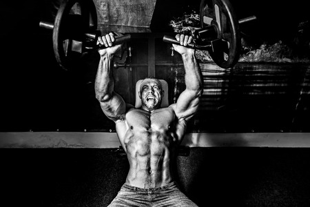 The athlete doing exercises on pectoral muscles in smoke. GYM