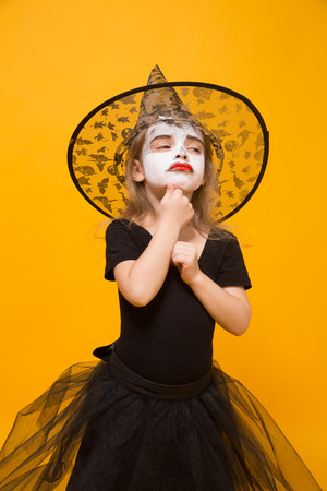 Small girl in Halloween witch costume, orange background.
