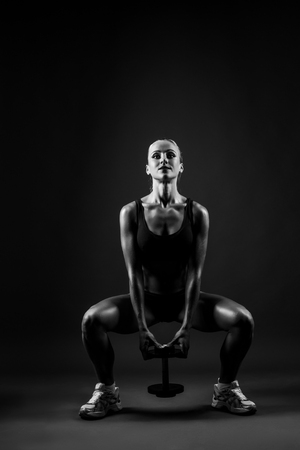 Beautiful muscular woman doing leg exercise on a dark gray background in studio.
